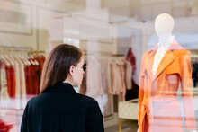 Woman In Front Of Clothing Store Shop Window.