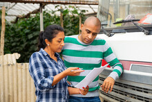 Two Hispanic Greenhouse Workers Signing Documents And Talking Near Car Outdoors