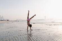 A Girl Doing A Somersault On The Beach