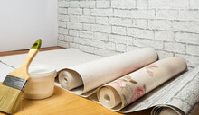 Multicolored Rolls Of Wallpaper, Brush, Glue, Paint Ready For Renovation In The Apartment Room. Do-it-yourself Apartment Renovation Concept