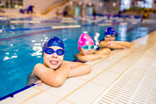 Disabled Boys And Girl With Down Syndrome In Swimming Cap With Goggles