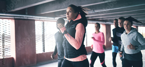Fototapeta premium Attractive young urban runner pacing her team