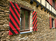 Old Castle Windows With Typical Red And Black Shutters. The Facade Is Made Of Sandstone And Half-timbered. Castle Schoenburg, Oberwesel, Rhineland-Palatinate.