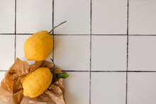 Two Big Lemons With A Green Leaf In A Torn Brown Shopping Craft Paper Bag On A White Tile Kitchen Countertop Background. Minimal Flat Lay With Copy Space. Healthy Immune Support Concept.