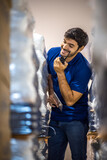 Fototapeta Na ścianę - foreman who is working in warehouse storehouse warehouse factory using walkie-talkie communication, checking store stock, working concept in uniform. worker