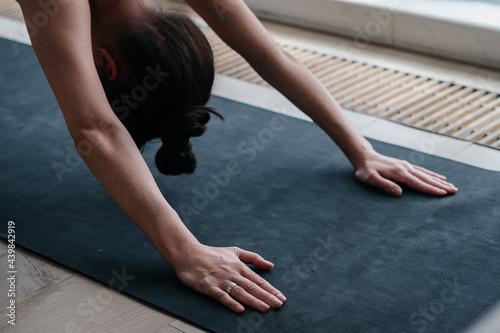 Slika na platnu Cropped view of woman performing downward facing dog yoga position