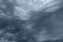 Blue And Dark Grey Heavy Clouds In The Sky Before A Thunderstorm. Dramatic Backdrop Or Wallpaper. Natural Dangerous Menacing Background. Ahead Of A Storm Or Cataclysm. High Quality Photo