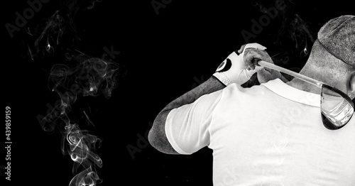 Rear view of senior male golf player swinging gold club against smoke effect on black background