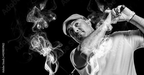 Senior caucasian male golf player swinging golf club against smoke effect on black background