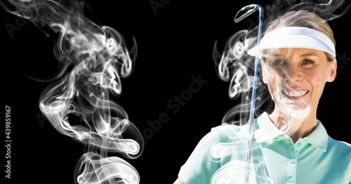 Senior caucasian female golf player holding golf club against smoke effect on black background