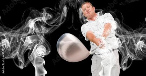 Caucasian male golf player swinging golf club against smoke effect on black background