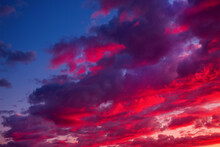 Evening Sky With A Crescent Moon And Red And Purple Clouds, Colored By The Sunset Rays.