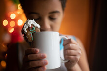 Child Drinks From Mug With Gingerbread House