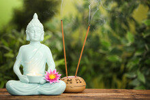 Buddha Statue With Burning Candle And Lotus Flower Near Incense Sticks On Wooden Table. Space For Text
