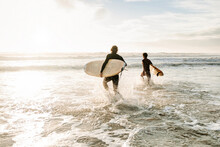 Anonymous Surfer Friends At The Beach With Surfboards