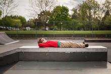 Boy Lying Down On Skate Park Ramp