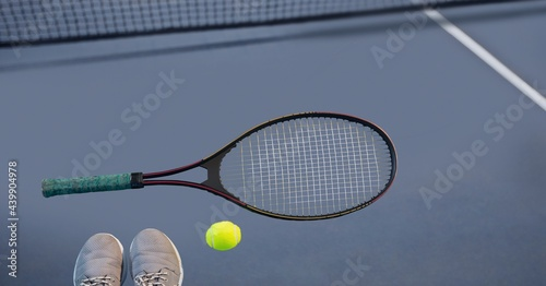 Composition of tennis ball, sports shoes and racket on tennis court