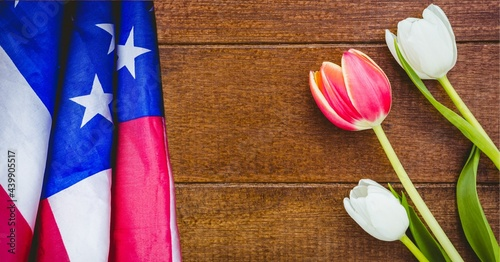 American flag and pink and white tulip flowers on wooden background