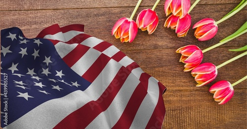 American flag and pink tulip flowers on wooden background