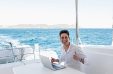 Man Browsing Laptop On Deck Of Yacht