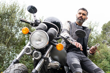 Focused Hispanic Male Rider Sitting On Motorcycle Parked In Nature And Using Smartphone
