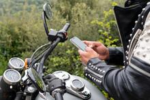 Stylish Male Biker Browsing Smartphone In Nature