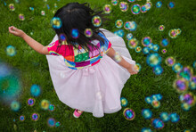 Young Girl Twirling In Bubbles