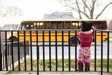Little Girl Watching A School Bus Drive Off