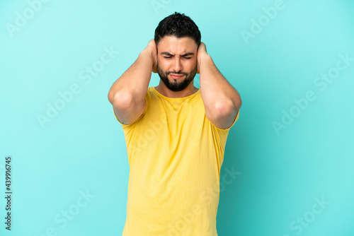 Fotografie, Tablou Young arab man isolated on blue background frustrated and covering ears
