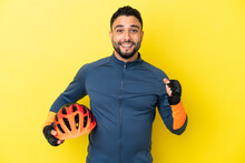 Young Cyclist Arab Man Isolated On Yellow Background Celebrating A Victory In Winner Position