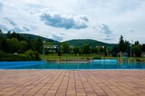 Swimming pool with a playground for children against the backdrop of the mountains
