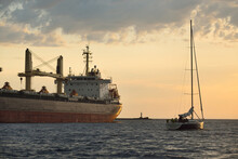 Large Cargo Ship (bulk Carrier, 179.99 Meters Length) And Sloop Rigged Yacht Sailing In The Baltic Sea At Sunset. Freight Transportation, Global Communications, Economy, Cruise, Recreation. Sport