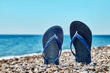 Blue Flip-flops On The Pebble Beach With Turquoise Sea And Blue Sky In Background. Summertime. Vacation Concept.