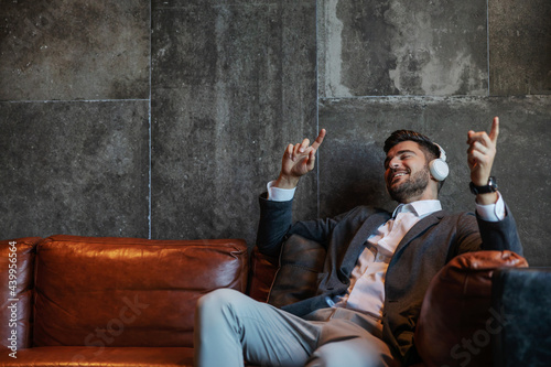 Obraz na plátně A businessman sitting on the couch in front of a gray wall with headphones on and enjoying the online music