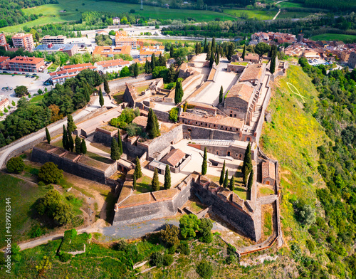Scenic aerial view of medieval walled Castle on hilltop on background of small Spanish village of Hostalric in green spring valley, Girona, Catalonia Fototapeta