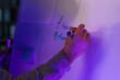 Leinwandbild Motiv Young man writing on flipchart in office at night