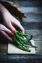 Women�s Hands Put Green Asparagus On A Cutting Board