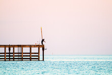 Fisherman Lowering A Crab Pot From Jetty In Wallaroo
