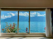 Woman Wearing Sunglasses Seen Through Window Against Lake