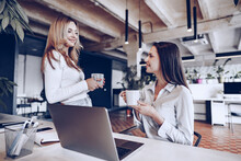 Two Young Women Colleagues Drinking Coffee In Office