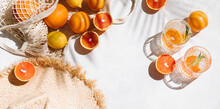 Summer Fashion Flat Lay Banner On White Background. Holiday Party, Vacation, Travel, Tropical Concept. Straw Hat, Refreshing Drinks And Citrus Fruits. Palm Shadow And Sunlight, Sun. Top View.