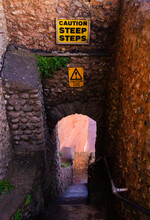 Caution Steep Steps At The Top Of Castle Steps Going Down Between Dark Red Stone Walls