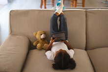 Happy African American Girl Sitting Upside Down On Couch Using Tablet, With Teddy Bear