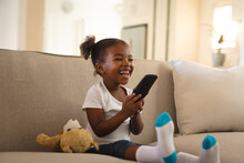 Laughing African American Girl Sitting On Couch With Teddy Bear, Holding Remote Control, Watching Tv