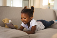 Happy African American Girl Lying On Couch With Teddy, Using Tablet And Smiling