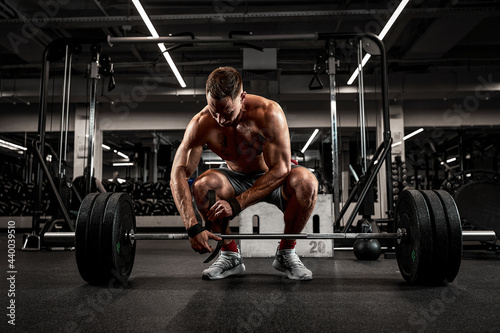 Tela Athlete, bodybuilder exercise with a barbell, athlete prepares the barbell for e