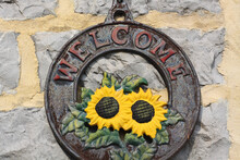 Closeup Shot Of A Metal Welcome Sign With Sunflowers And Welcome Hanging On The Wall