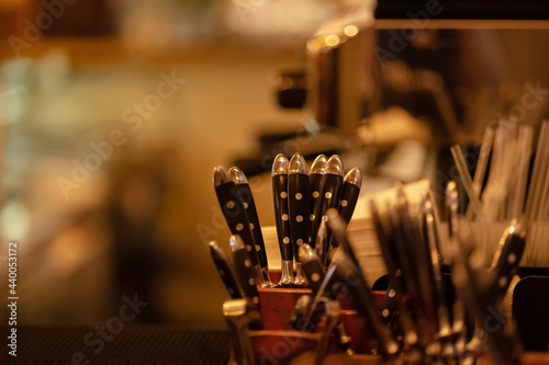 Cutlery stands in a wooden stand in a kitchen cuisine, cafe, restaurant, bistro in warm light Fotobehang