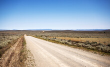 Dirt Road In An Arid Landscape With Distant Hills