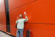 Leinwandbild Motiv cheerful man in sweatshirt taking selfie on smartphone and showing peace sign near orange wall and longboard.